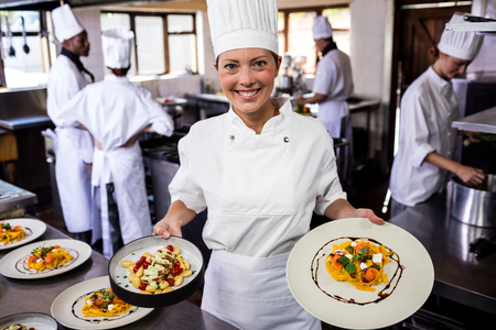 Female chef holding plate of prepared pasta in kitchen at hotel