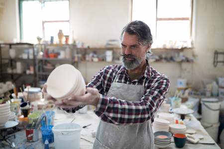 Focused male potter examining his creation for flaws in the pottery workshop Stock Photo
