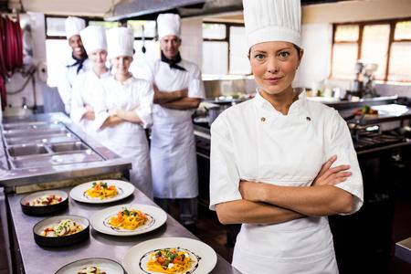 Chef mujer de pie con los brazos cruzados en la cocina del hotel