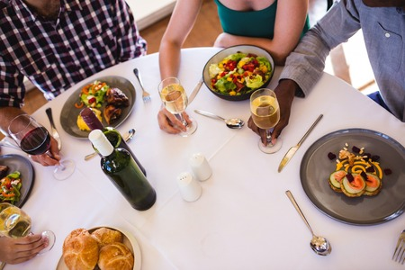 High angle view of friends enjoying food and wine at table in restaurant