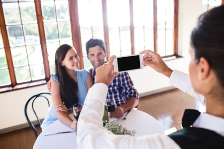 Waitress clicking photo of a young couple in restaurant