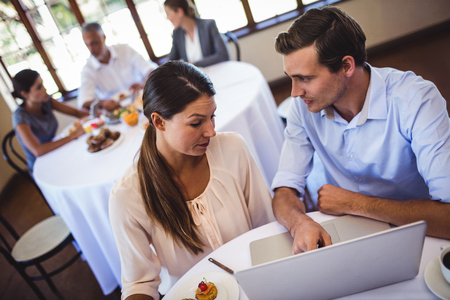 Couple discussing on laptop at table restaurant Stock Photo