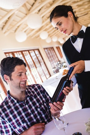 Waitress showing wine to customer at table in restaurant