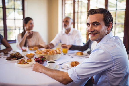 Smiling businessman looking at camera in restaurant