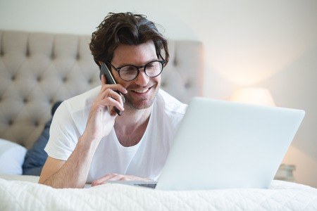 Man using laptop while talking on mobile phone at home