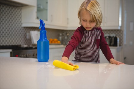 Boy cleaning kitchen worktop with rag at home
