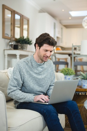 Man using laptop in living room at home Banco de Imagens