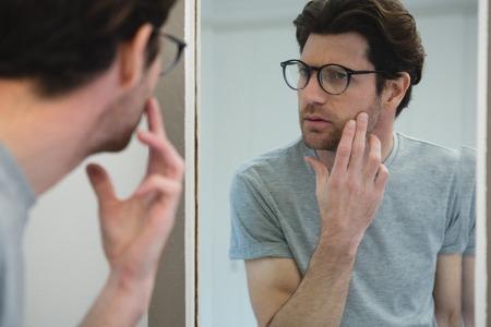 Man kijkt zijn gezicht in de spiegel thuis Stockfoto
