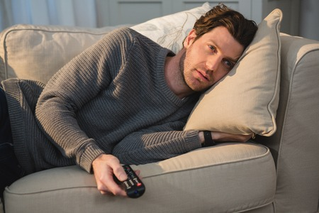 Man watching television in living room at home