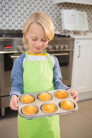 Boy holding a tray of muffins at home Stock Photo