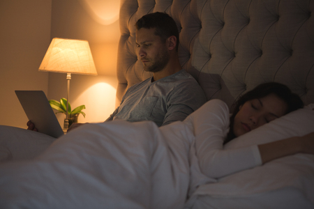 Man using laptop while woman sleeping in bedroom at home
