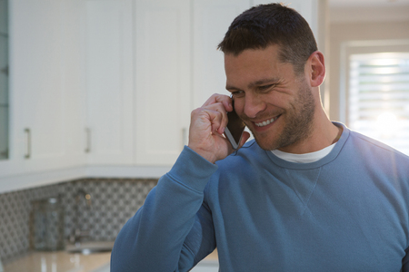 Man talking on mobile phone in kitchen at home
