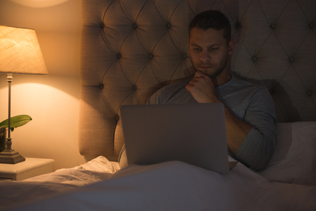 Man using laptop in bedroom at home
