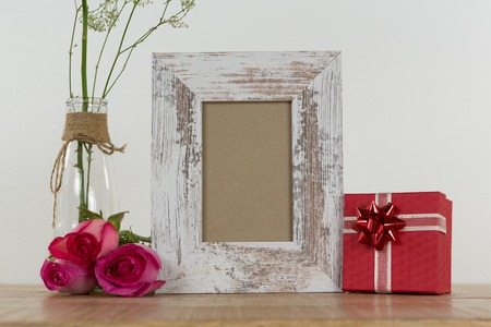 Rose flower, empty photo frame and gift boxes on wooden table