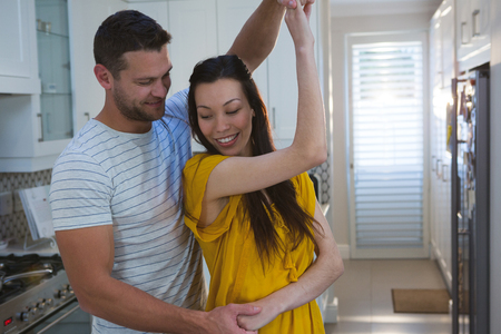 Couple dancing together in kitchen at home