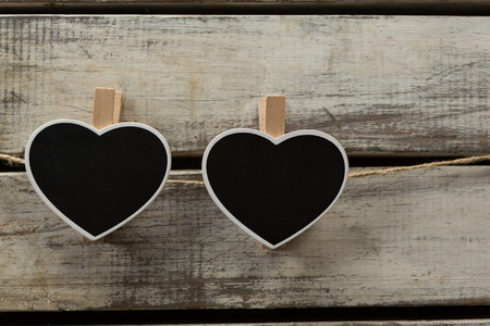 Heart shape decorations hanging on thread against wooden plank Archivio Fotografico