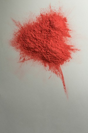 Overhead of red color powder on white background
