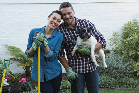 Portrait of couple with their dog in the garden