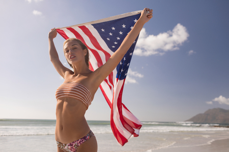 Low angle view of young woman holding waving American flag at beach on a sunny day