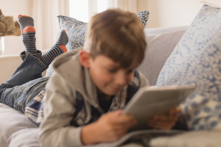 Close up of young boy lying on his front while using digital tablet in living room at home Stock Photo
