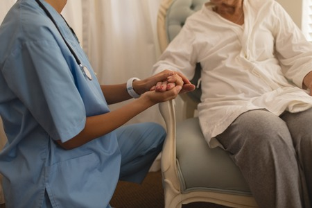 Mid section of beautiful female physician consoling senior woman and holding her hand at home