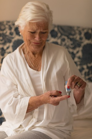 Front view of a senior woman applying cream on her finger in bedroom at home