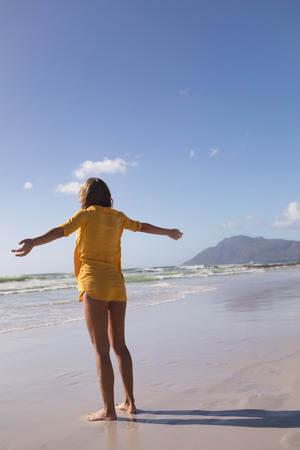 Rear view of woman standing with arms outstretched at beach in the sand