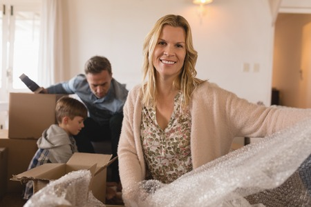 Portrait of happy mother smiling with her family in the background unpacking cardboard boxes in their new home Stock Photo