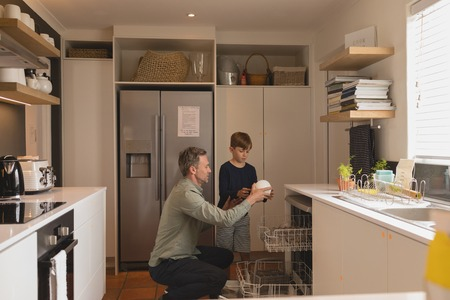 Front view of father and son doing chores together taking out clean dishes out of the dish washer Stock Photo
