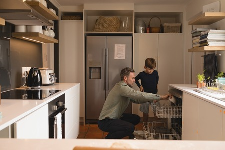 Side view of father teaching son how to load up the dishwasher with dirty dishes
