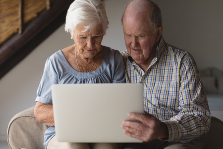 Front view of a senior couple using digital tablet in living room at home Reklamní fotografie
