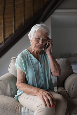 Front view of a senior woman talking on mobile phone while sitting on a sofa in living room at home