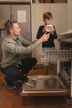 Side view of father and son placing bowl in dishwasher in the kitchen at home