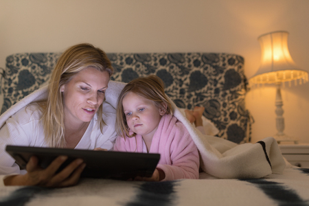 Front view of sweet mother and daughter using digital tablet in bedroom at home
