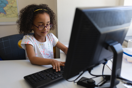 Front view little black schoolgirl concentrates and using desktop pc at desk in classroom of elementary school Banco de Imagens