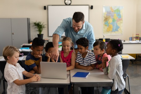 Front view of a male teacher teaching kids on laptop in classroom of elementary school