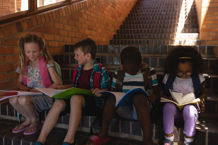 Front view schoolkids reading book while sitting on stairs of elementary school together