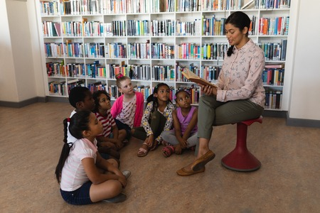 Side view of female teacher sitting on chair and reading a story schoolkids sitting on floor in school library