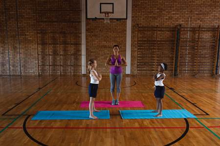 Front view of young female yoga teacher teaching yoga to school kids in school
