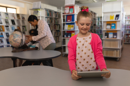 Front view of schoolgirl studying on digital tablet at table in school library