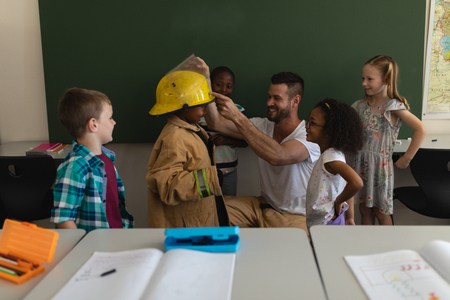 Front view of male Caucasian firefighter helps to wearing fire uniform to schoolkid with all the schoolkids around in classroom of elementary school