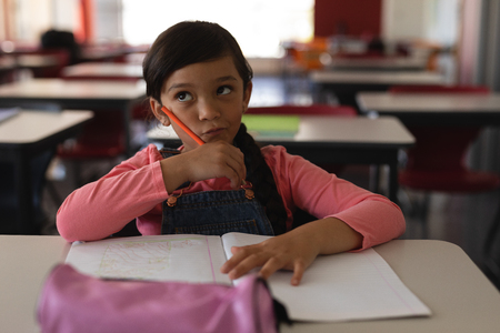 Front view of thoughtful schoolgirl studying in classroom sitting at desks in school 版權商用圖片