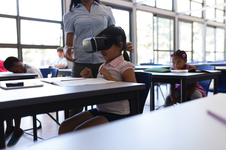 Side view of school girl using virtual reality headset at desk in classroom of elementary school