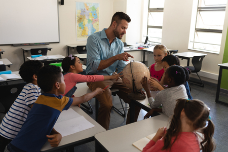 Male teacher teaching his kids about geography by using globe in classroom of elementary school