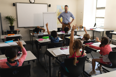 Achteraanzicht van schoolkinderen die hand opsteken in de klas van de basisschool
