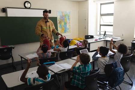 Front view of a schoolkids applauding while male Caucasian firefighter teaching about fire safety in classroom of elementary school