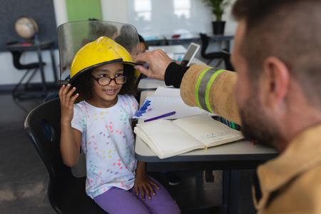 Front view of a Caucasian Firefighter wearing helmet to a black schoolgirl in classroom of elementary school