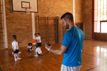 Side view of basketball coach using digital tablet at basketball court in school