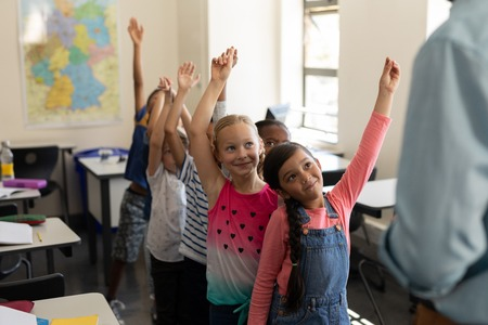 School kids standing in row and raising hand in classroom of elementary school