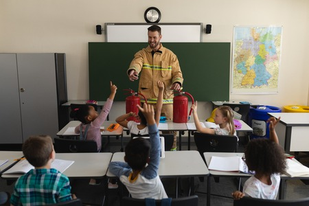 Front view of a schoolkids raising hands while male Caucasian firefighter teaching about fire safety in classroom of elementary school 写真素材